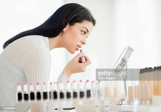 USA, New Jersey, Jersey City, Young woman applying lipstick