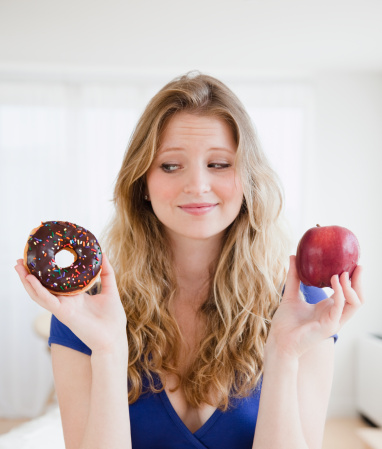 USA, New Jersey, Jersey City, Young woman choosing between donut and apple - gettyimageskorea