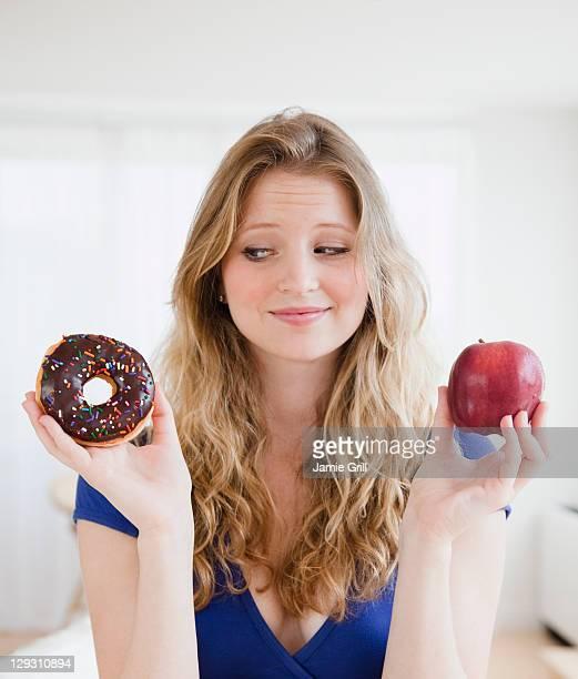 usa, new jersey, jersey city, young woman choosing between donut and apple - entscheidung stock-fotos und bilder
