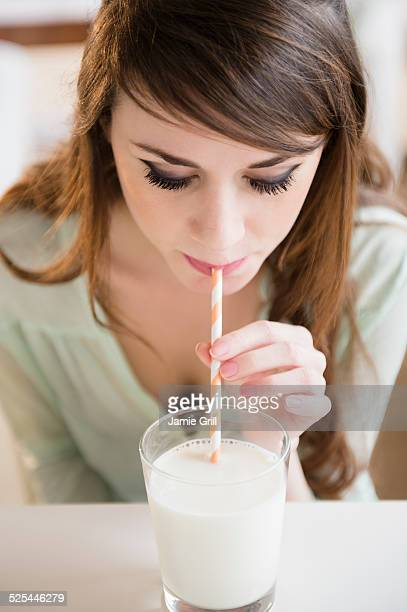 USA, New Jersey, Jersey City, Young woman drinking milk with straw