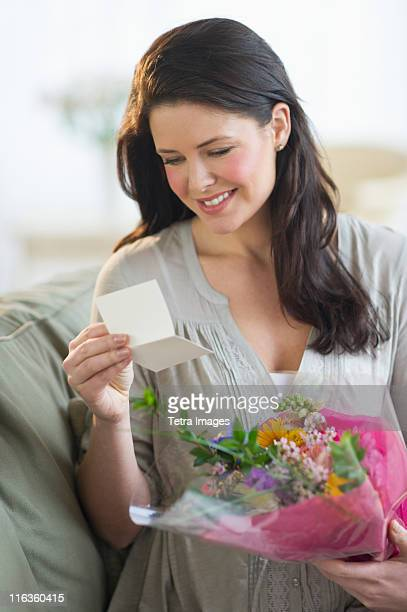 USA, New Jersey, Jersey City, young woman holding bouquet and reading greeting card