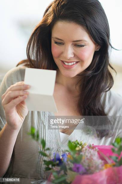 usa, new jersey, jersey city, young woman holding bouquet and reading greeting card - mothers day card ストックフォトと画像