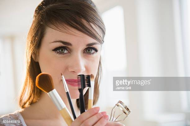 USA, New Jersey, Jersey City, Young woman holding make-up accessories