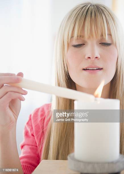 USA, New Jersey, Jersey City, young woman igniting candle