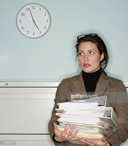 USA, New Jersey, Jersey City, young woman in office holding stack of documents