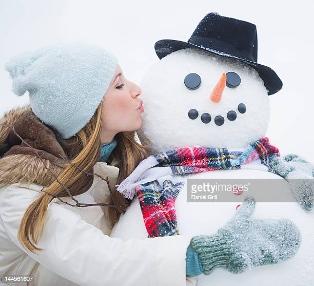 USA, New Jersey, Jersey City, young woman kissing snowman
