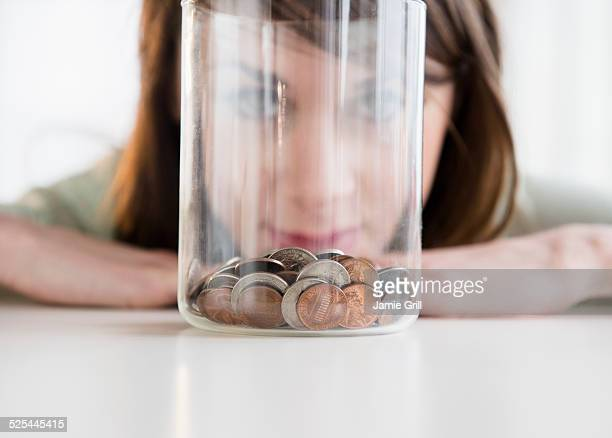 USA, New Jersey, Jersey City, Young woman looking at coins in jar