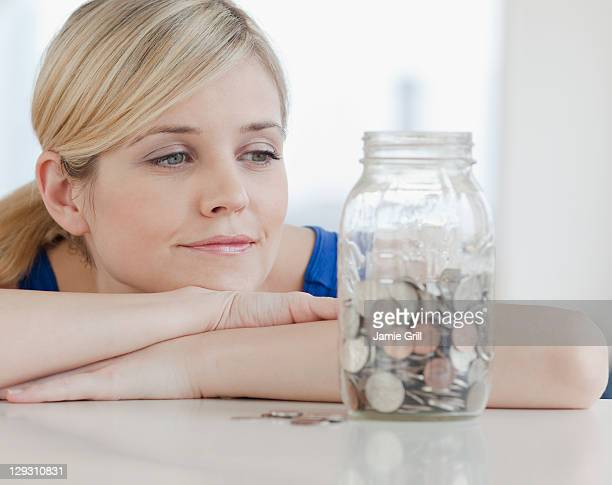 USA, New Jersey, Jersey City, Young woman looking at jar with coins in it