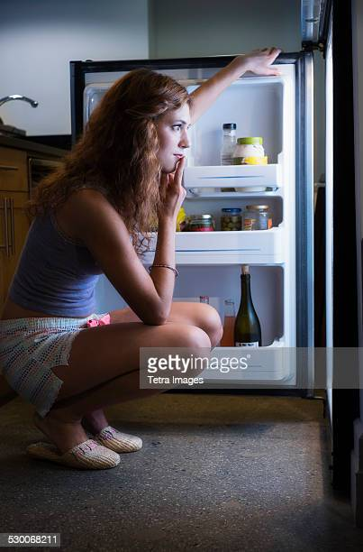 usa, new jersey, jersey city, young woman looking into refrigerator - midnight stock pictures, royalty-free photos & images