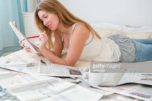 USA, New Jersey, Jersey City, Young woman lying on bed and doing job search
