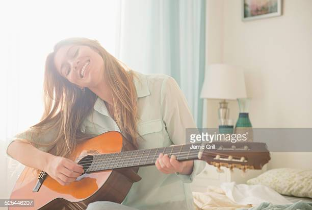 usa, new jersey, jersey city, young woman playing acustic guitar on bed - plucking an instrument stock pictures, royalty-free photos & images