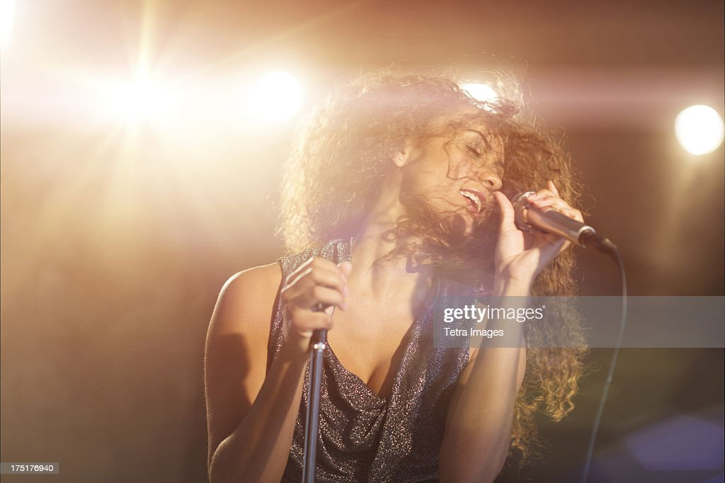 USA, New Jersey, Jersey City, Young woman singing in spotlight : Foto de stock