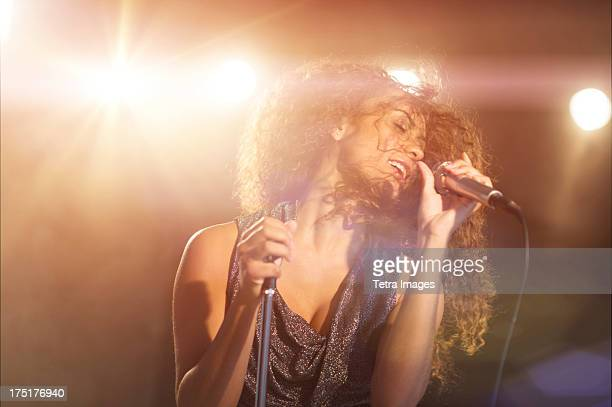 usa, new jersey, jersey city, young woman singing in spotlight - singer stock pictures, royalty-free photos & images