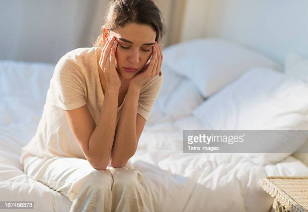 USA, New Jersey, Jersey City, Young woman sitting on bed with headache