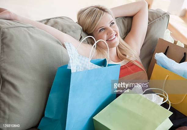 USA, New Jersey, Jersey City, Young woman sitting on sofa surrounded by shopping bags