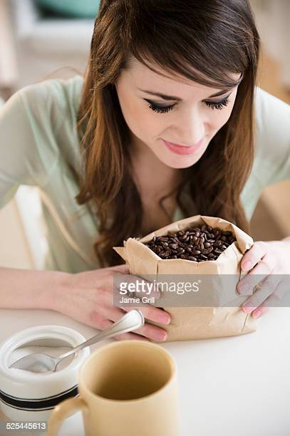 USA, New Jersey, Jersey City, Young woman smelling coffee beans