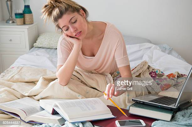 usa, new jersey, jersey city, young woman studing in bed - day in the life stock photos and pictures