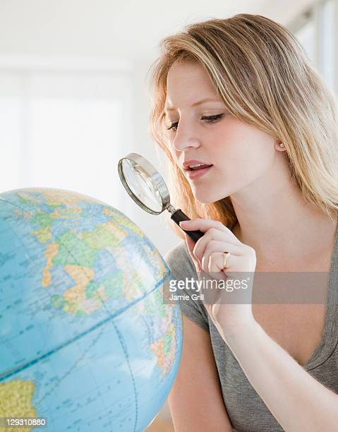 USA, New Jersey, Jersey City, Young woman with magnifying glass searching on globe