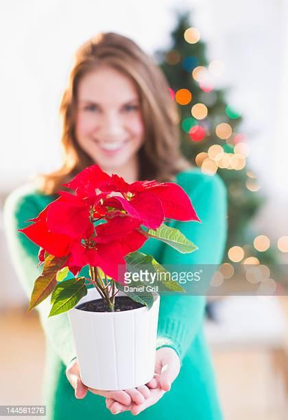 USA, New Jersey, Jersey City, Young woman with red poinsettia
