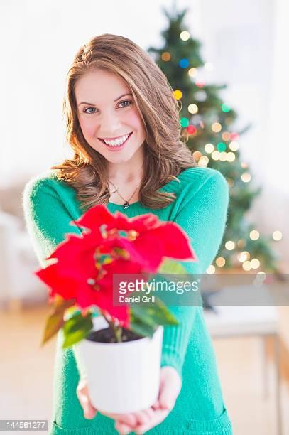usa, new jersey, jersey city, young woman with red poinsettia - flor de pascua fotografías e imágenes de stock