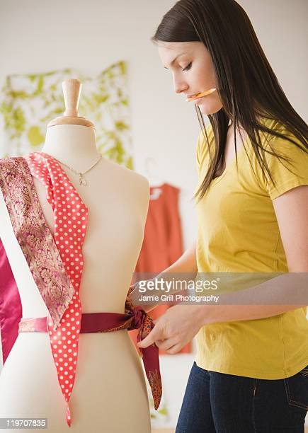 USA, New Jersey, Jersey City, Young woman working with dressmakers model