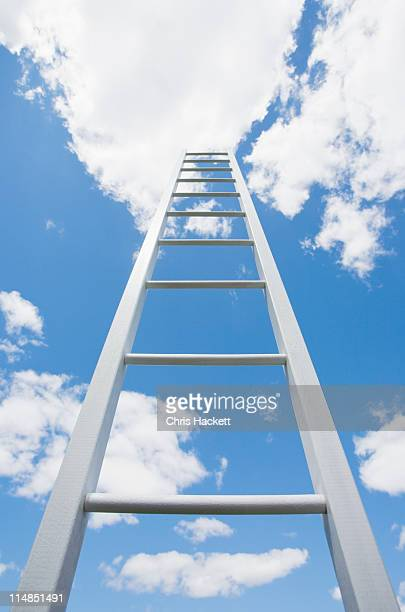 USA, New Jersey, ladder reaching cloudy sky