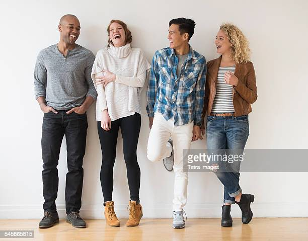 usa, new jersey, laughing friends standing against white wall - four people stock pictures, royalty-free photos & images