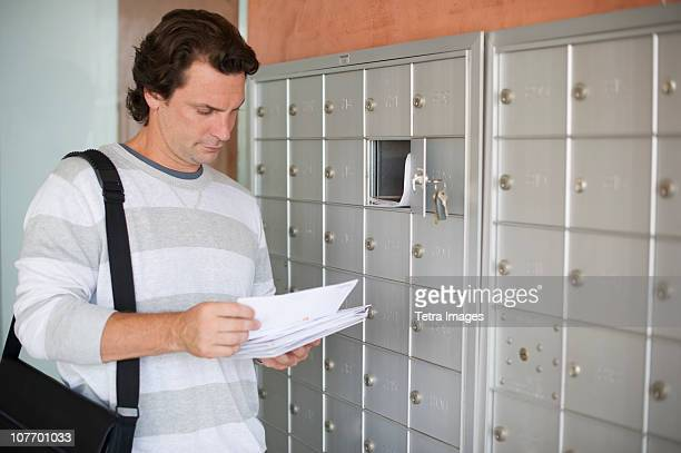 USA, New Jersey, Man standing next to mailboxes and checking post