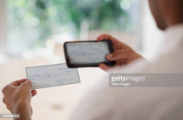 USA, New Jersey, Man taking photo of banking check with cell phone