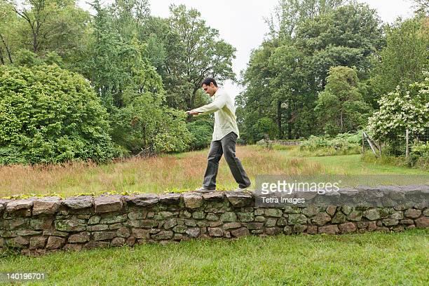 USA, New Jersey, Man walking on stone wall on field