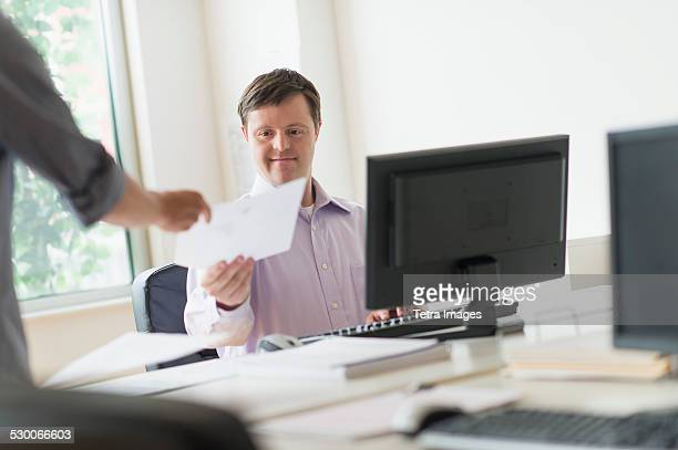 USA, New Jersey, Man with down syndrome working in office