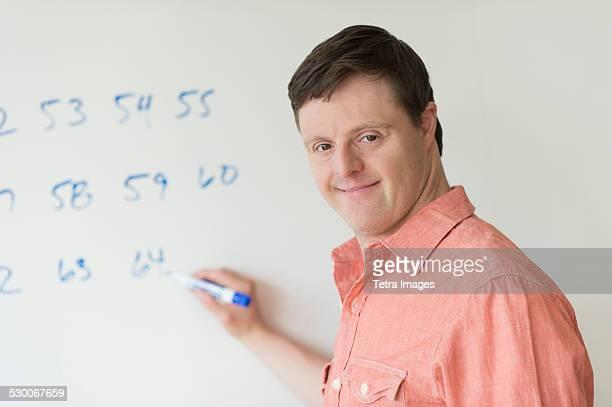 USA, New Jersey, Man with down syndrome writing on whiteboard