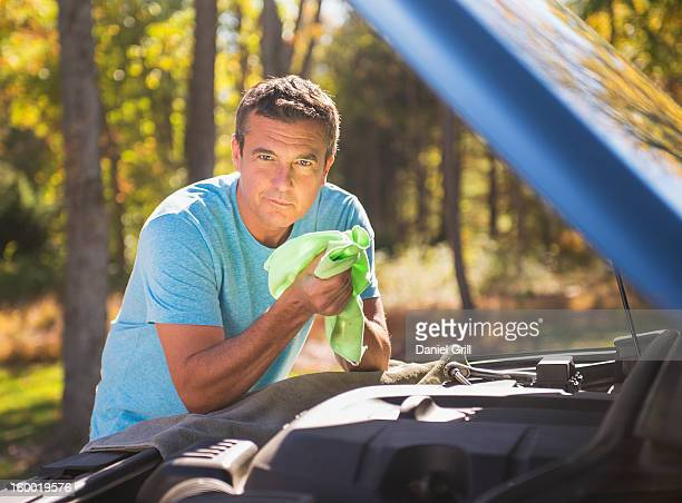 USA, New Jersey, Mendham, Man leaning on car and wiping his hands