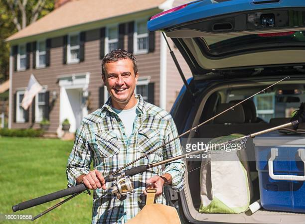 USA, New Jersey, Mendham, Portrait of man holding fishing rods in front of packed car