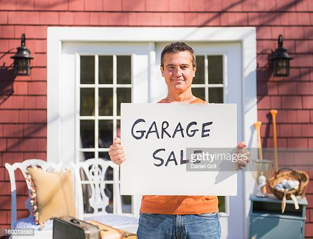 usa, new jersey, mendham, portrait of man holding garage sale sign - garage sale stock pictures, royalty-free photos & images