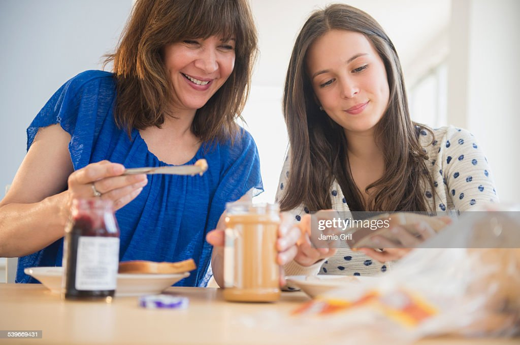 USA, New Jersey, Mother and daughter (14-15) making peanut butter and jelly sandwiches : Stock Photo
