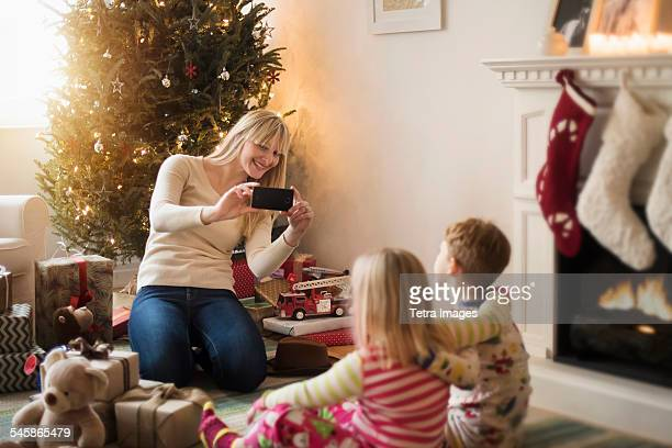 USA, New Jersey, Mother with children (4-5, 6-7) opening christmas presents and taking photos