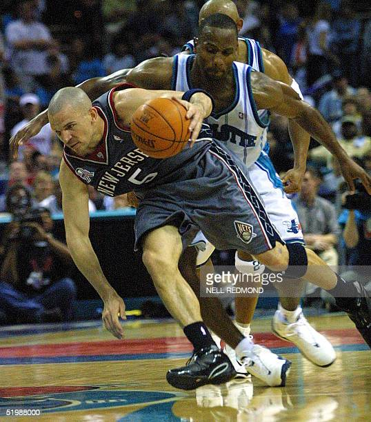 New Jersey Nets' guard Jason Kidd keeps his balance as he drives past Charlotte Hornets' forward George Lynch in the second half of game four in the...