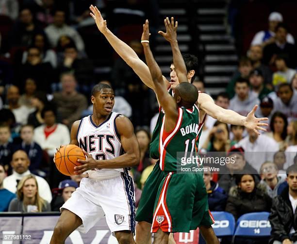 New Jersey Nets small forward Damion James looks to pass around Milwaukee Bucks point guard Earl Boykins and Milwaukee Bucks power forward Ersan...