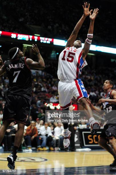 New Jersey Nets' Vince Carter is defended by Philadelphia 76ers' John Salmons and Kevin Ollie during game at Continental Airlines Arena Carter scored...