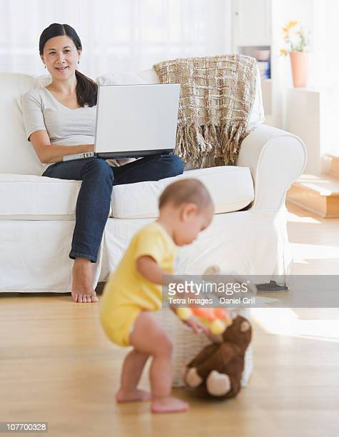 usa, new jersey, new jersey city, baby boy (6-11 months) playing, mother sitting on sofa and using laptop - 6 11 months stock pictures, royalty-free photos & images