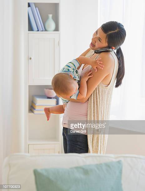usa, new jersey, new jersey city, mother carrying son (6-11 months) and talking on phone - 6 11 months stock pictures, royalty-free photos & images