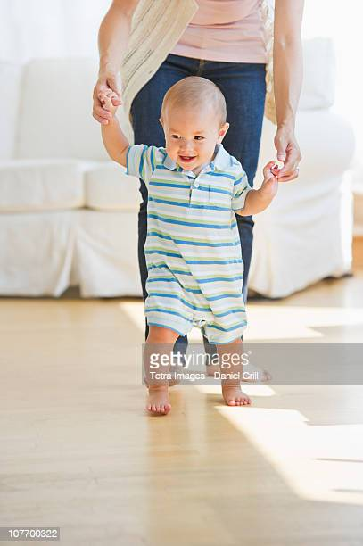 USA, New Jersey, New Jersey City, Mother helping son (6-11 months) with first steps