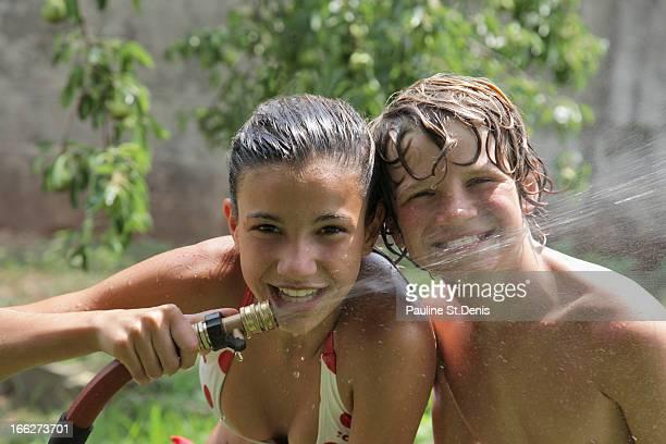 usa, new jersey, old wick, boy (10-11) playing with water hose in summer - ontbloot bovenlichaam fotos stockfoto's en -beelden