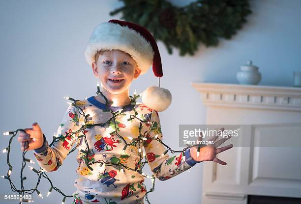 USA, New Jersey, Portrait of boy (6-7) holding christmas lights