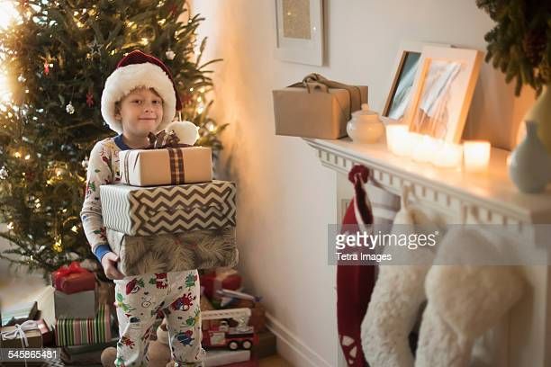 USA, New Jersey, Portrait of boy (6-7) wearing santa claus hat and carrying presents