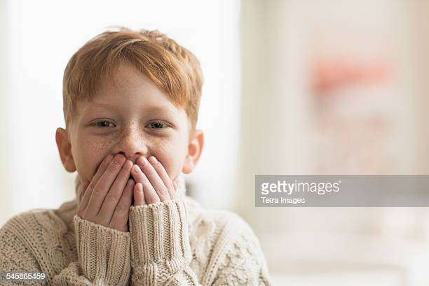 USA, New Jersey, Portrait of boy (6-7) with hands covering mouth