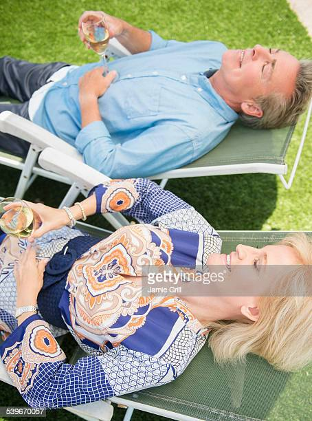 USA, New Jersey, Portrait of couple relaxing on sun loungers on lawn