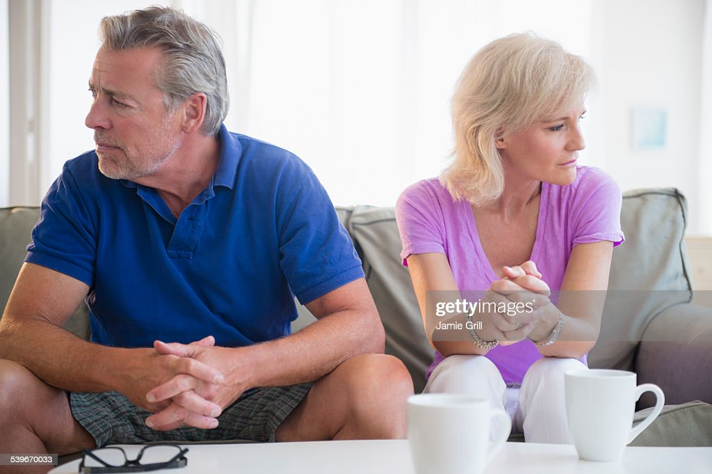 USA, New Jersey, Portrait of couple sitting on sofa, looking away from each other : Stock Photo