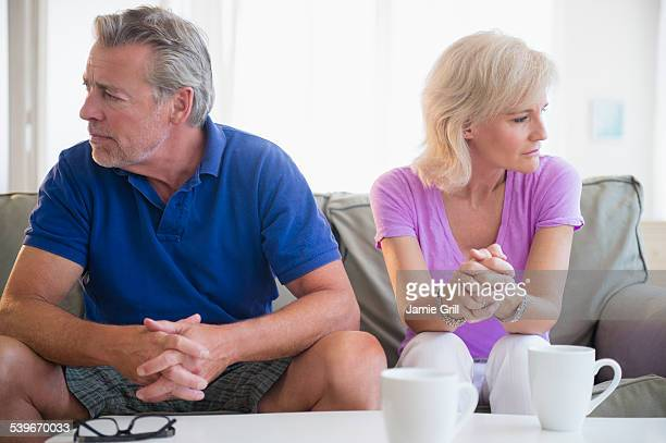 USA, New Jersey, Portrait of couple sitting on sofa, looking away from each other